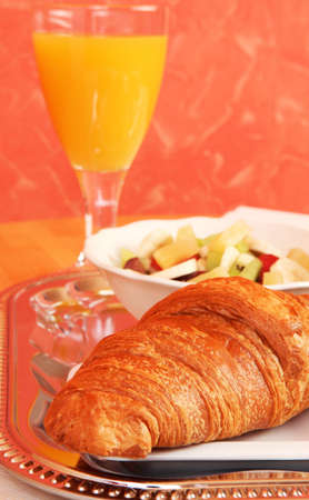 Still life of healthy breakfast with croissant, glass of orange juice and fruit salad