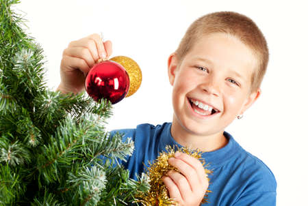 Young boy holding Christmas decorations and smiling, Christmas tree in foreground