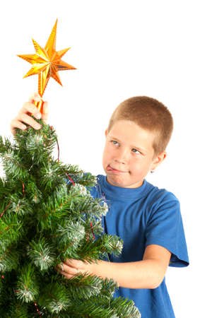 Young boy grimacing while decorating Christmas tree, studio shot with copyspace Stock Photo