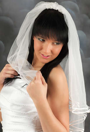 Young bride in white wedding dress looking down and smiling photo