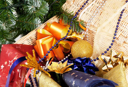 Close-up view of Christmas ornaments in wickered basket, Christmas tree in the corner Stock Photo
