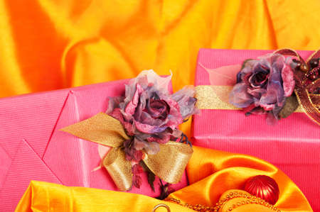 Close-up view of two luxurious pink Christmas presents over golden background