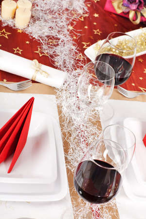 High angle view of Christmas decorated table, with red wine and plates