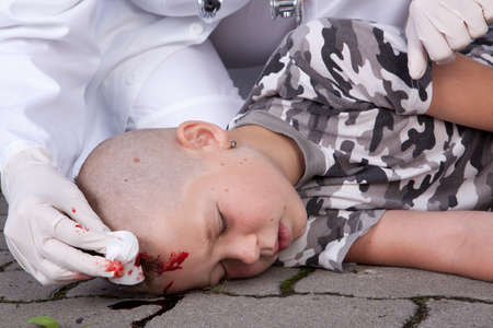 wounded: A lying boy in coma after accident with injured head, doctor nearby  Stock Photo