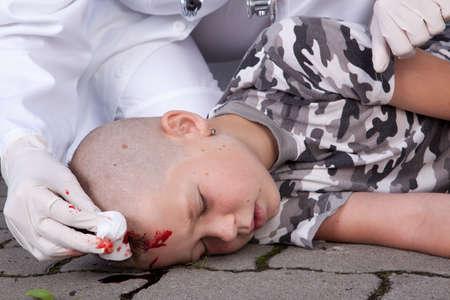 hemorragias: Un muchacho a en estado de coma despu�s de accidente con cabeza lesionado, el m�dico cercano  Foto de archivo