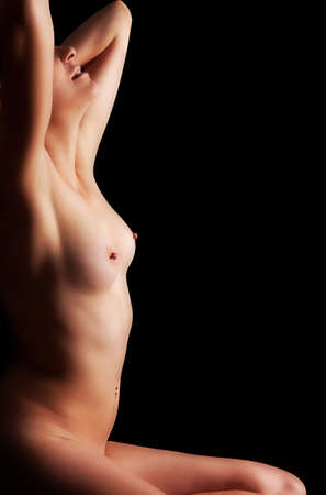 Portrait of an young naked and beautiful woman, over black background