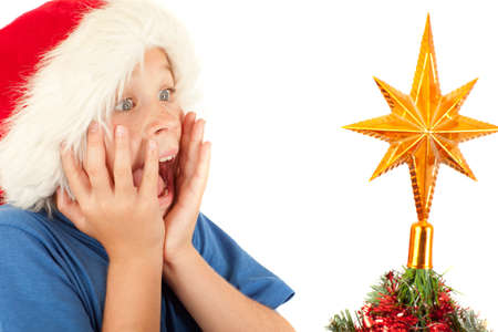 Young boy is excited while looking at Christmas tree with copyspace