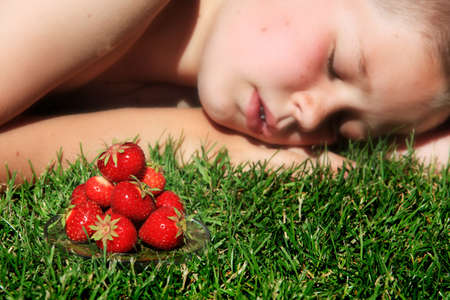 Boy sleeping on grass with pile of ripe strawberries in foreground.