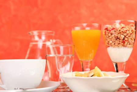 A healthy breakfast consisting of a fruit salad, glass of juice, coffe, cereals, yogurt and a glass of water Stock Photo