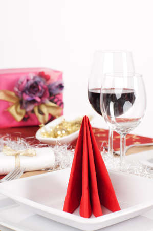 Close-up view of red napkin arranged on white plate, with Christmas present on white background Stock Photo