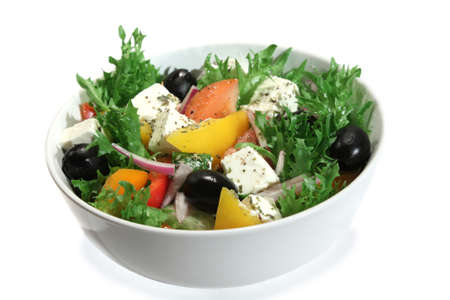 Appetizing greek salad with feta cheese in a bowl. Close up. Isolated on white Imagens