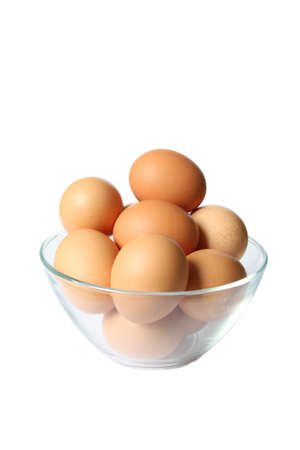 Colored eggs in glass bowl. Isolated on white. 免版税图像