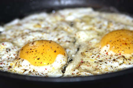 Spicy fried eggs in pan, sunny side up photo