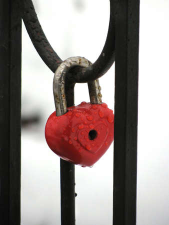 door lock love: Red heart lock with the drops of rain. Metal fence Stock Photo