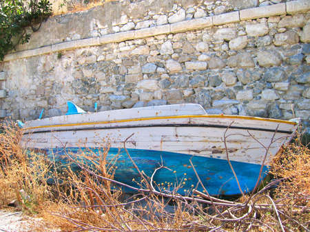 old wooden boat, behind a wall photo