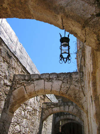 Narrow street with stone arches and old lantern. Rhodes Stock Photo - 4716329
