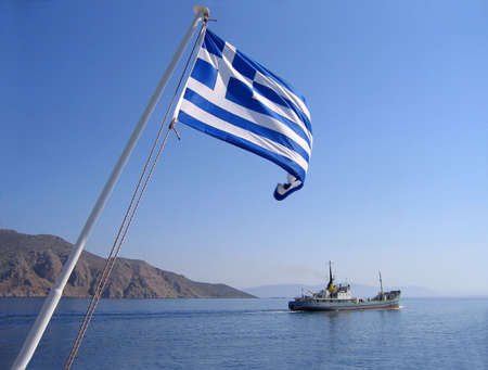 Sea view with greek flag, mountain and cargo ship photo