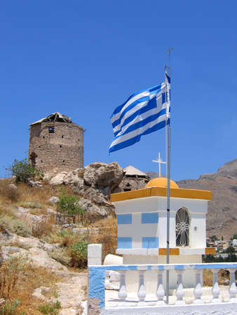 Greek flag, chapel and ancient ruined windmill. Moutain view at Kalymnos island photo