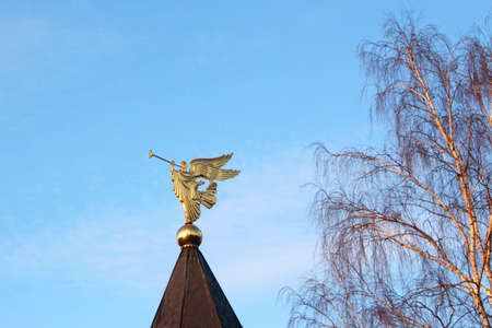 Golden figure of the Archangel with the pipe in the background of sky and tree photo