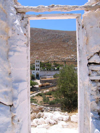 View of mountain and belfry of the Greek church, through the doorway of ancient fortress. Island of Kalymnos photo