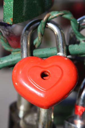 prisoner of love: Red heart lock hanging on metal fence Stock Photo