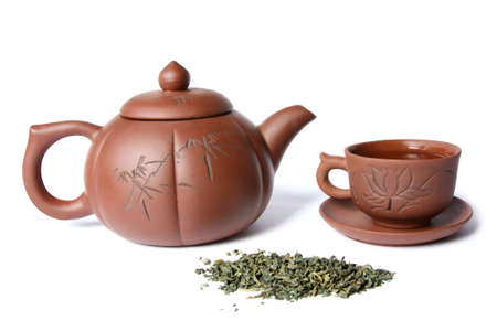 Teapot, teacup and a pile of green tea. Isolated on white Stock Photo
