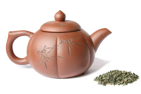 Teapot and a pile of green tea. Isolated on white Stock Photo