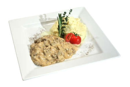 A beef stroganoff meal with mashed potatoes and tomato. Decorated with thime and rosemary. Isolated on white