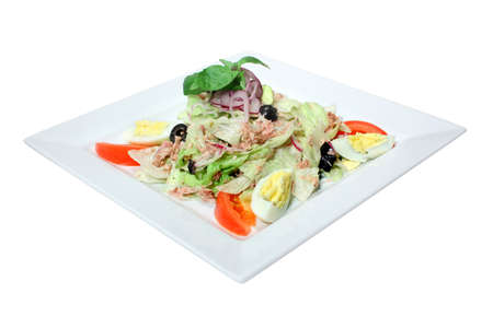 Nicoise Salad with tuna, tomatoes, hard boiled eggs and lettuce. Decorated with olives, onion and basil. Isolated on white