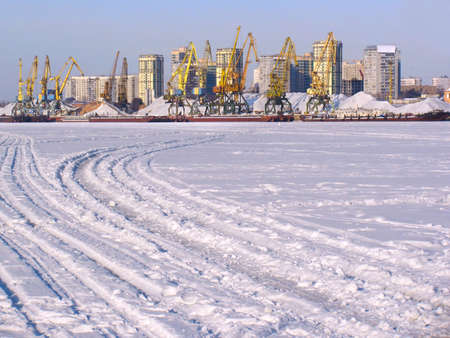 Cargo harbour on the frozen river with tracks on foreground photo