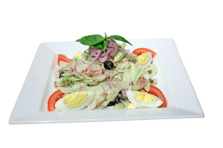 Nicoise Salad with tuna, tomatoes, hard boiled eggs and lettuce. Decorated with olives, onion and basil. Isolated on white photo