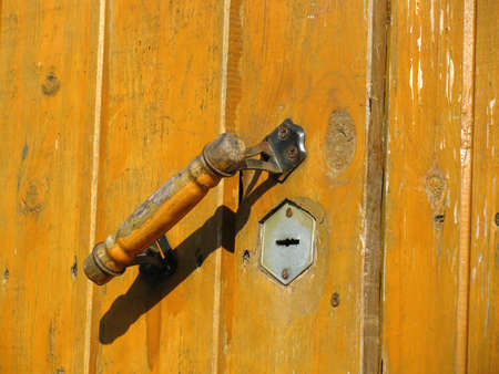 Old wooden weathered door with doorhandle and keyhole photo