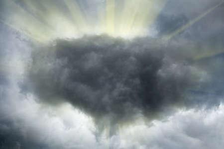 Sun shines trough dark stormy clouds