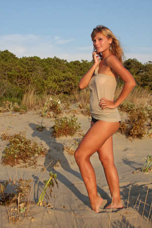 Beautiful young blonde woman standing at the beach