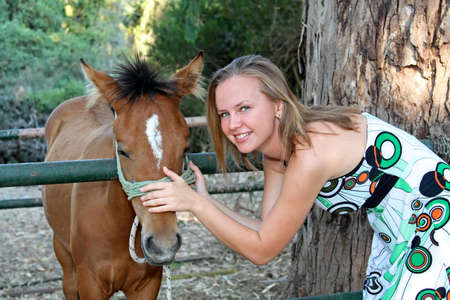Smiling young woman with a foal photo