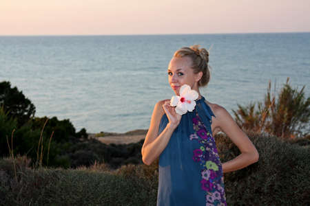 Portrait of a beautiful young blonde woman at the sea shore photo