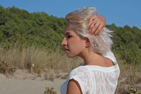Young blonde woman standing at the beach Stock Photo - 10879319