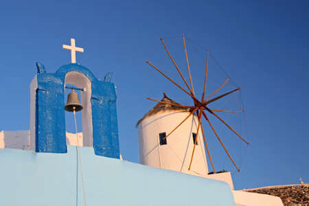 Old Greek windmill and orthodox chapel in Santorini island, Greece photo