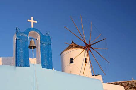 Old Greek windmill and orthodox chapel in Santorini island, Greece photo