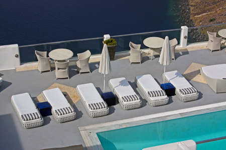 Row of pool chairs and umbrellas. Luxury hotel with caldera view at Santorini, Greece photo