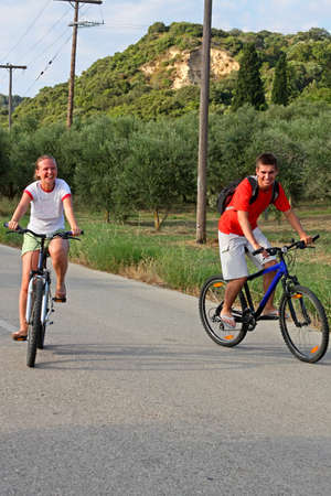 Young couple on bicycle ride through countryside in Mediterranean Europe photo
