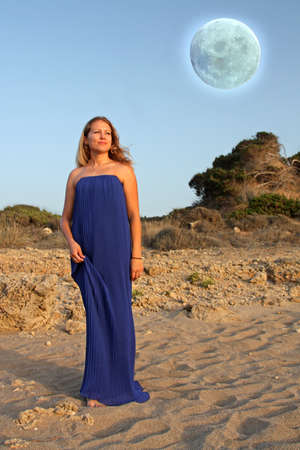 Young blonde woman walking on the beach. Full moon photo