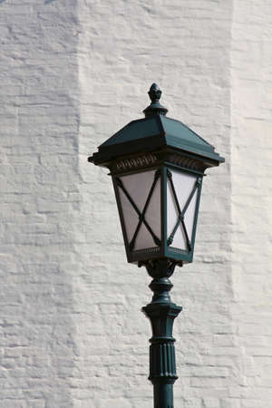 Old style street lamp in front of the wall of white brick.  photo