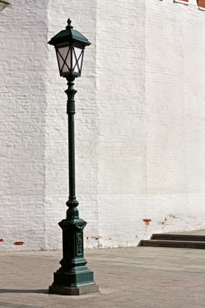 lamp post: Old style street lamp in front of the wall of white brick Stock Photo