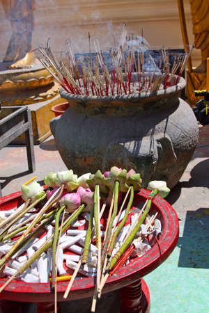 Offering in a Buddhist temple - lotus flowers and incense sticks photo