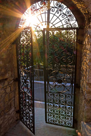 Sun shining through the bars of a wrought-iron gate photo