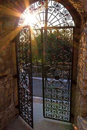 open gate: Sun shining through the bars of a wrought-iron gate