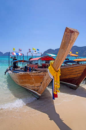 Longtail boats landing in Phi-Phi Island, Thailand photo