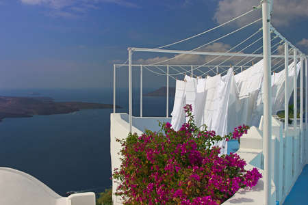 Towels drying on ropes at the edge of caldera in Santorini, Greece photo