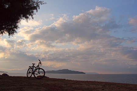 Silhouette of a mountain bicycle at the seashore  Twilight before the sunrise photo